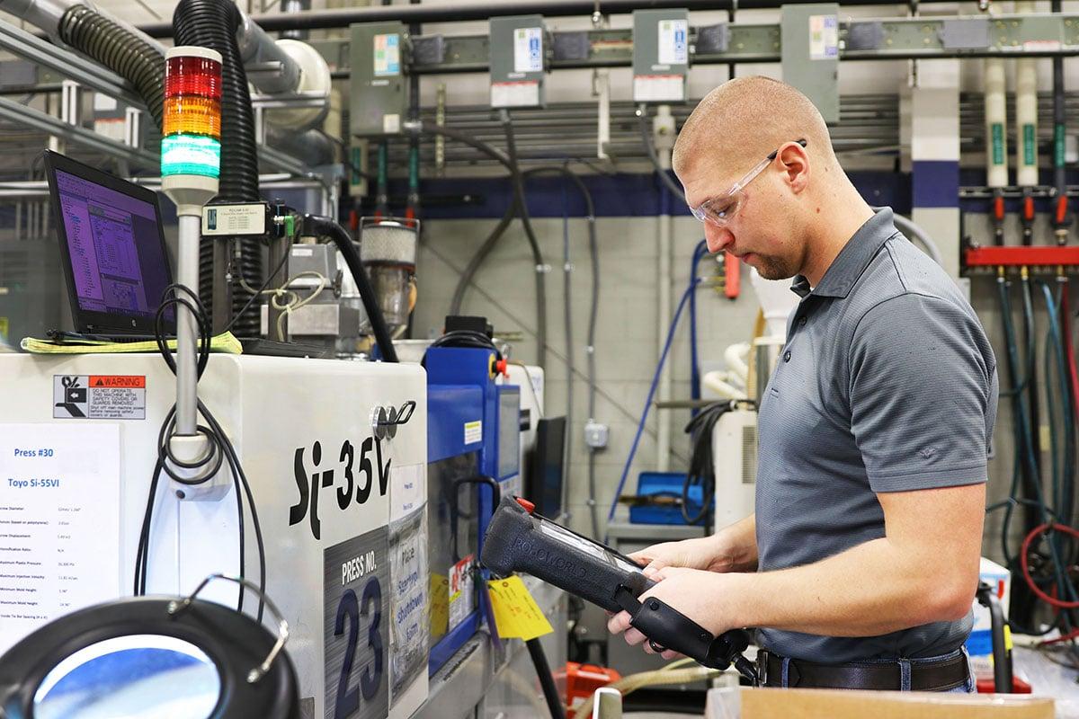 Kaysun employee programing a injection molding machine