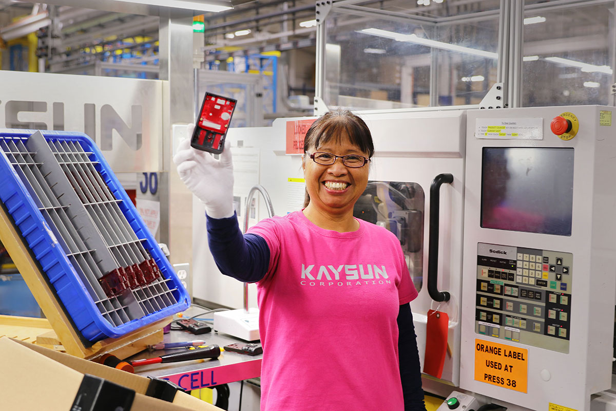 Person wearing a Kaysun Corporation t-shirt holding an injected molded part