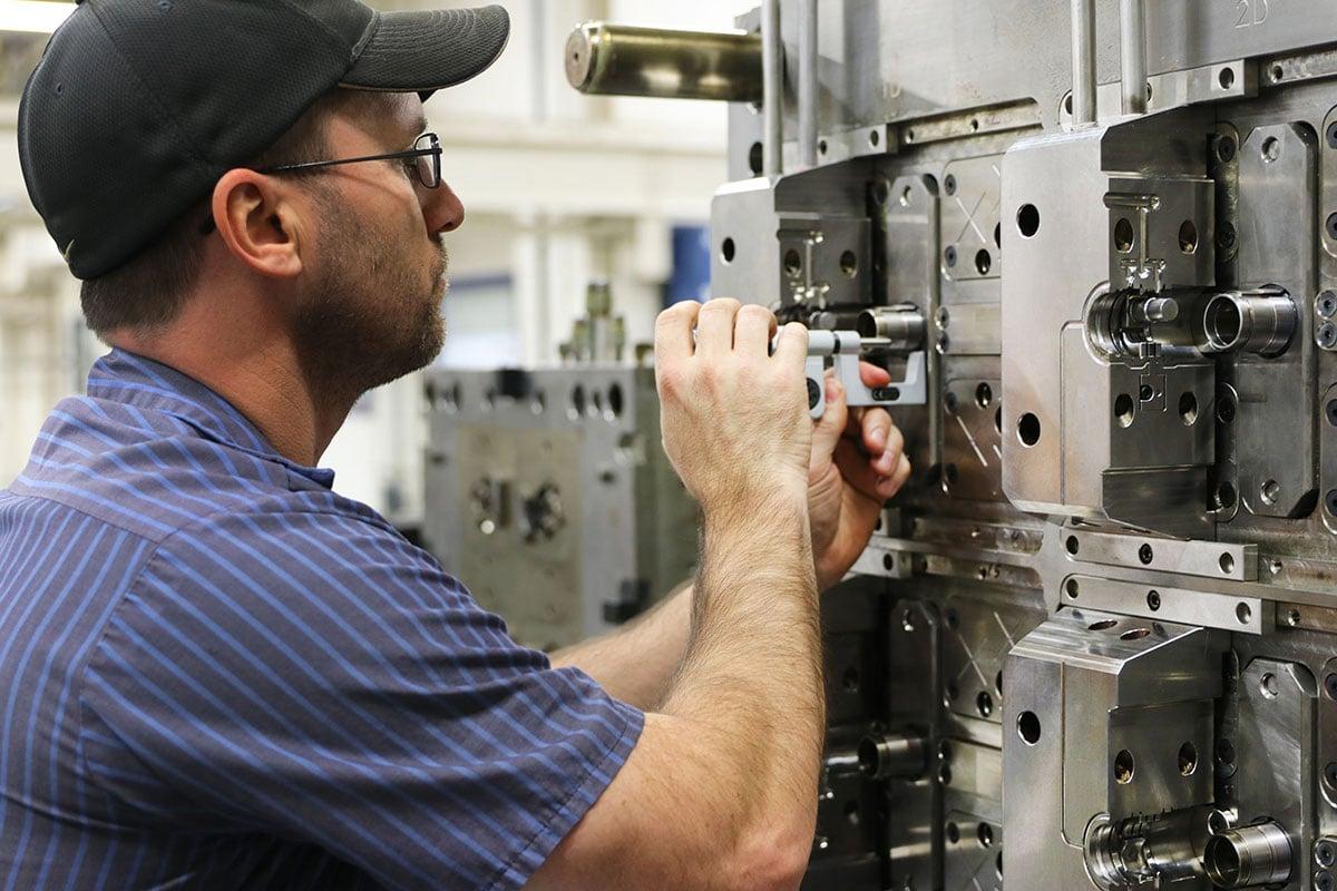 Kaysun employee working on an injection molding machine