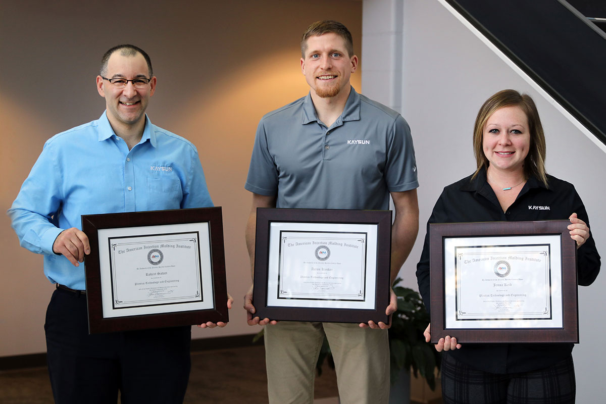 Three Kaysun employees holding up their American Injection Molding Institute degrees